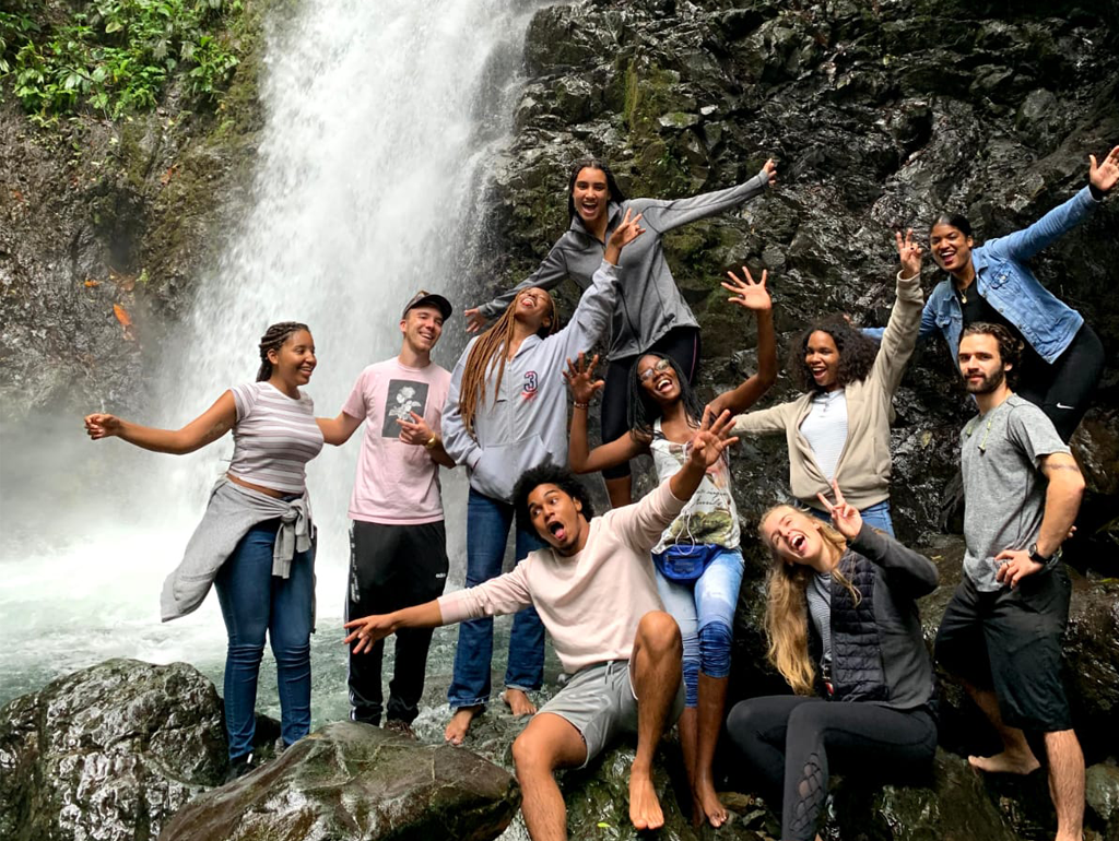 GW student Audrey Friedline poses with other students in front of a waterfall in Colombia.