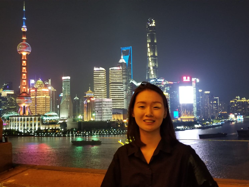 A Global Bachelor's student poses for a nighttime photograph at the waterfront in Shanghai.