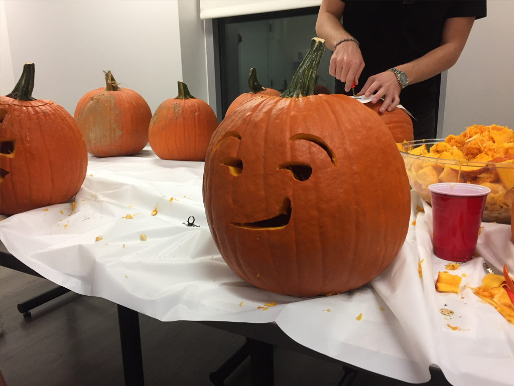 An exchange student carves a pumpkin into a Jack-o-Lantern during an event.