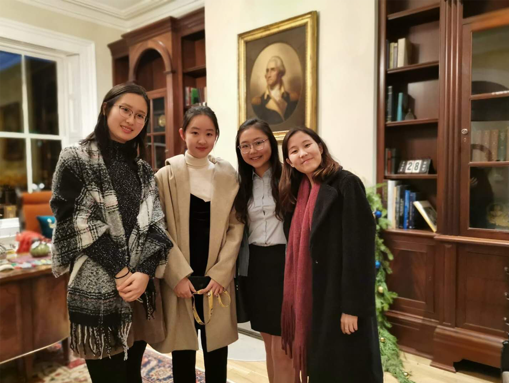 Four GW exchange students posing for a photo in front of a portrait of George Washington in the University President's office.