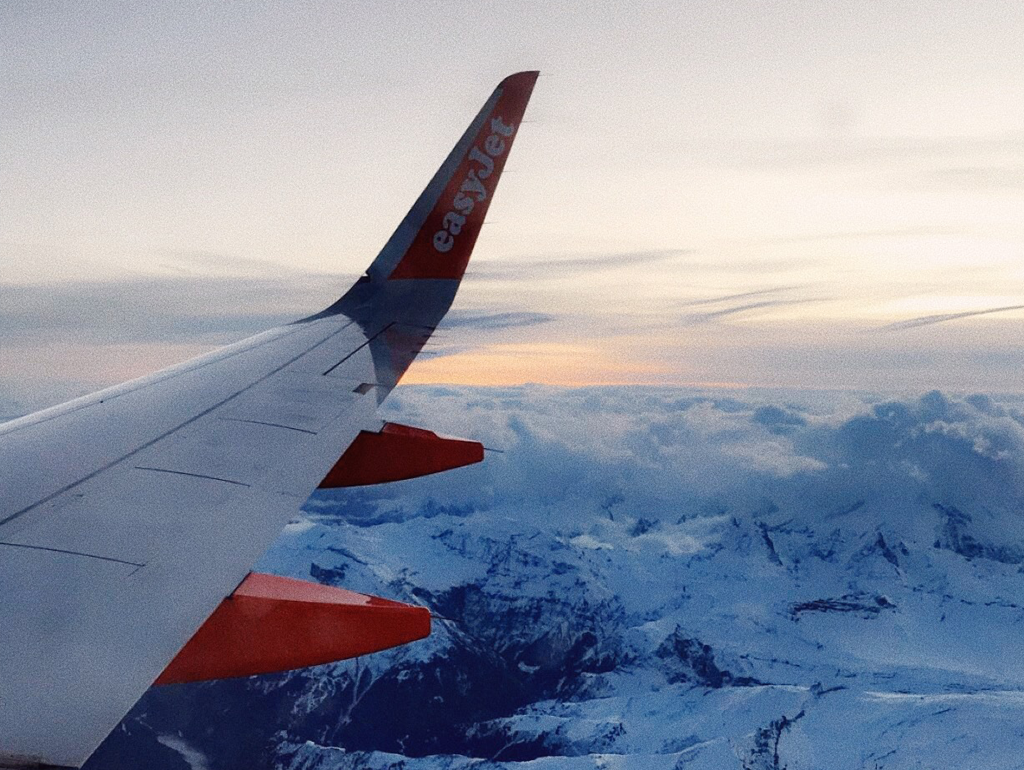 An EasyJet airplane wing is visible from high above a mountain range.
