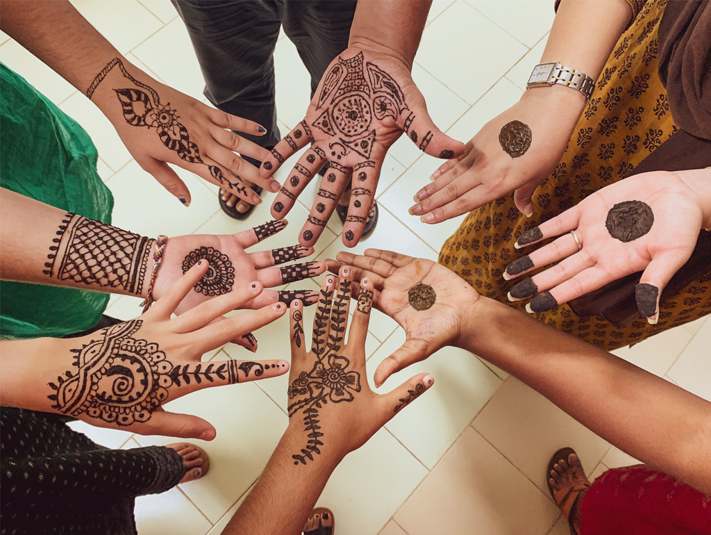 Students with henna artwork on their hands.