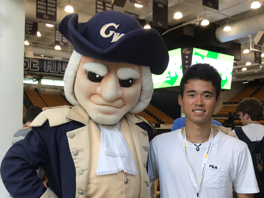 An exchange student posing with the GW mascot, George.