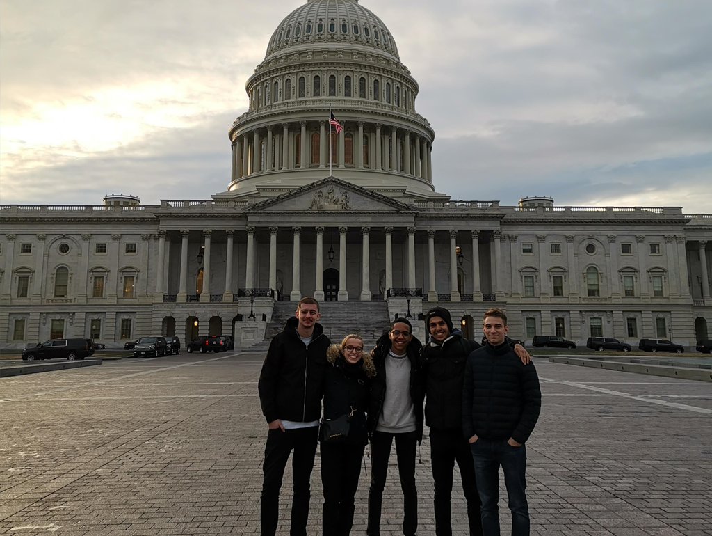 Five exchange students smile for a photo in front of the U.S. Capitol Building.