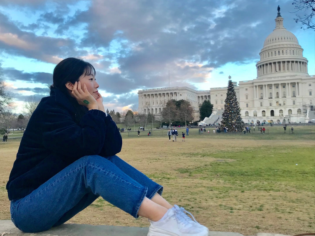 A GW exchange student sitting on a wall in front of the U.S. Capitol Building.